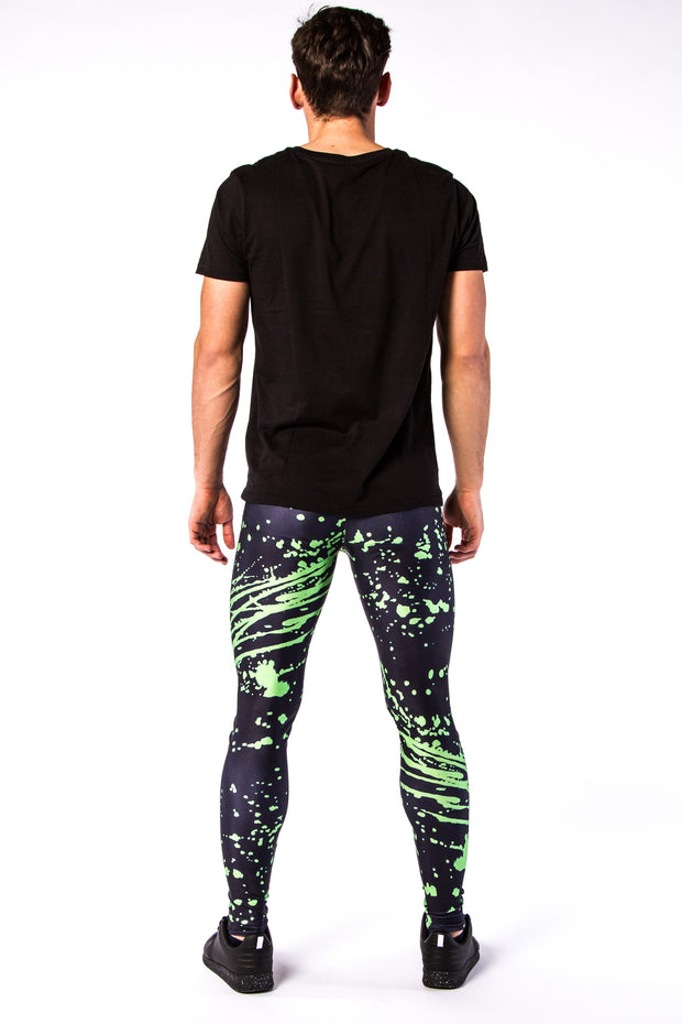 Man posing in Kapow Meggings black and electric green splattered men's leggings from behind