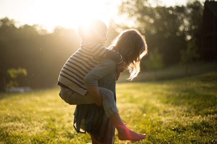 A woman carries a child on her back as they stand on the grass and are silhouetted by the setting sun