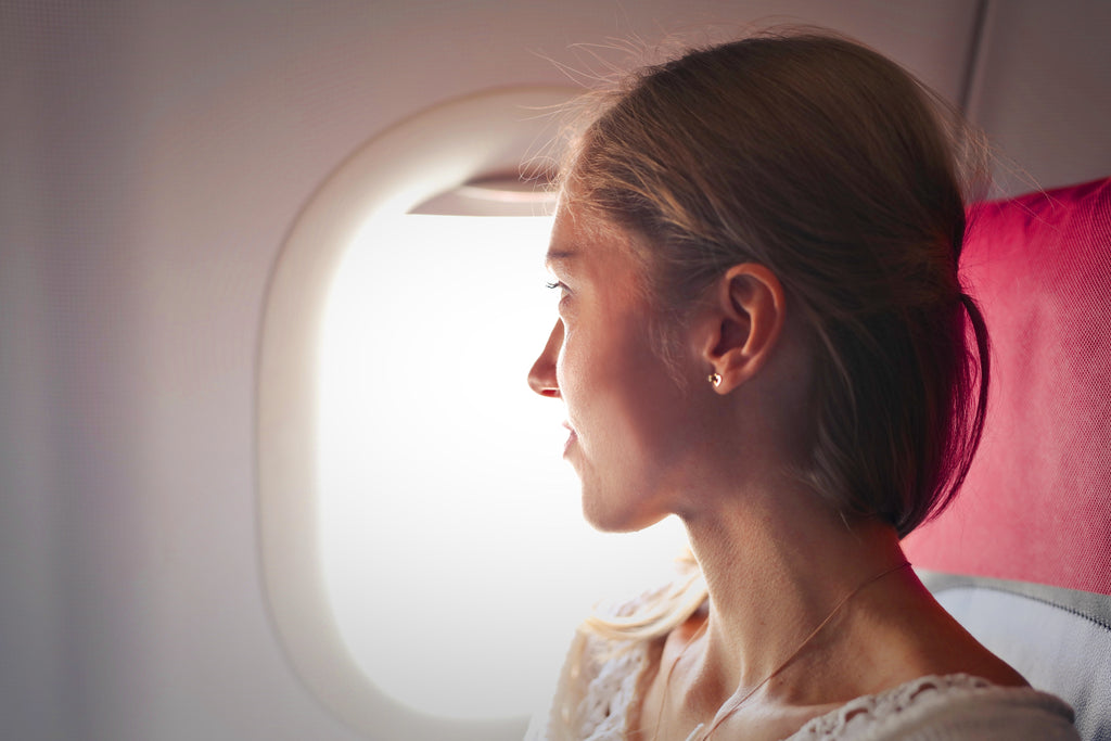 Woman sitting in the window seat on an airplane looking out the window