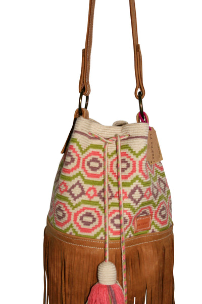 Close up image of Wayuu bucket bag purse with caramel brown leather strap, fringe with drawstring and tassels; bag is tan with light brown, light pink and light green circular design
