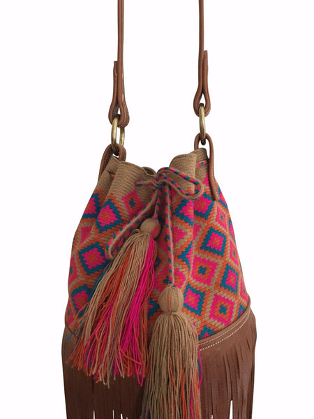 Close up image of Wayuu mochila purse with brown leather strap and fringe; bag is tan with magenta orange blue detail
