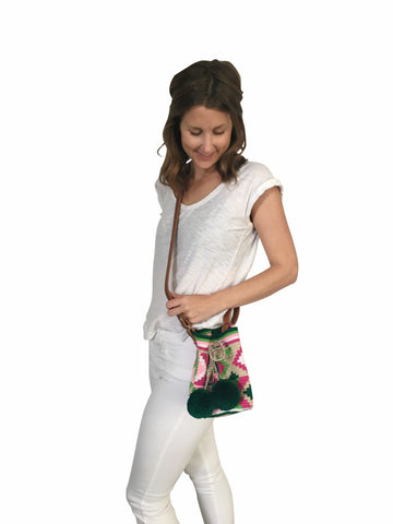 On body image of Wayuu mini mochila bucket bag purse with adjustable leather strap, drawstring and two pompoms; bag has geo patterns with multi colors