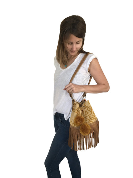 On body image of Wayuu bucket bag purse with brown leather strap and fringe and pompoms; bag is tan with mustard yellow design