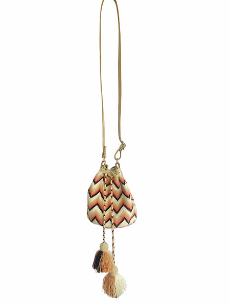 Image of Wayuu mini mochila bucket bag purse with adjustable leather strap, drawstring and two tassels; bag has white base with colorful horizontal zigzag design