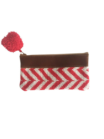 Image of handmade Wayuu zipper pouch with woven textile in red and white pattern; pouch has colorful pompom and leather at the top