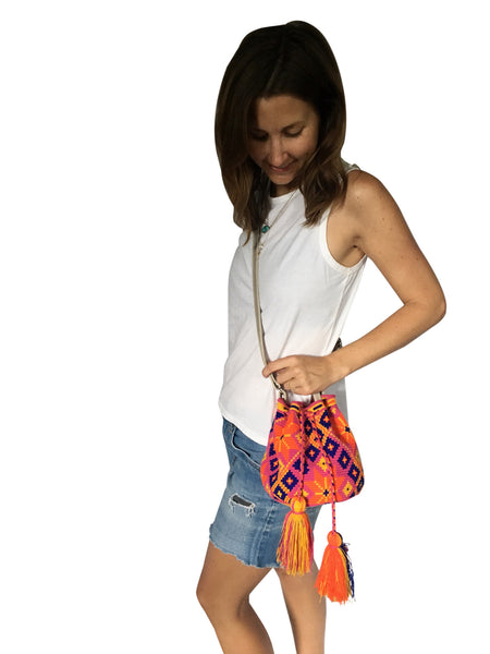 On body image of Wayuu mini mochila bucket bag purse with adjustable gray leather strap, drawstring and two tassels; bag is purple base with dark blue, yellow and orange geo design