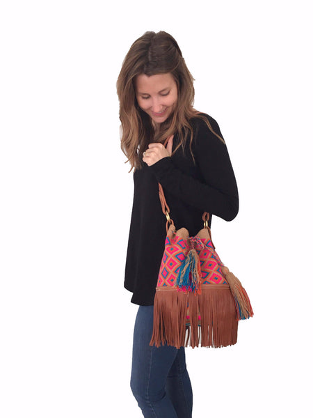 On body image of Wayuu mochila purse with brown leather strap and fringe; bag is tan with magenta orange blue detail