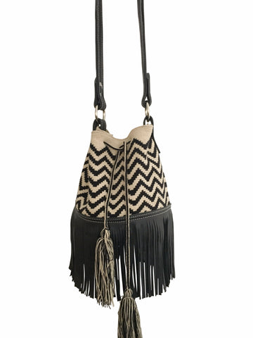 Image of Wayuu mochila purse with black leather strap and fringe; bag is tan with black zigzags