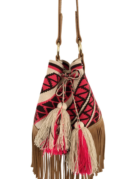 Close image of Wayuu bucket bag purse with brown leather strap and fringe; bag is tan with pink design