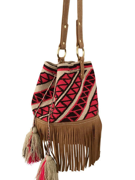 Side angel image of Wayuu bucket bag purse with brown leather strap and fringe; bag is tan with pink design