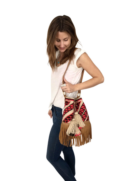 On body image of Wayuu bucket bag purse with brown leather strap and fringe; bag is tan with pink design
