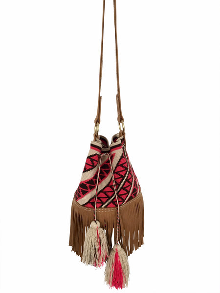 Full shot image of Wayuu bucket bag purse with brown leather strap and fringe; bag is tan with pink design