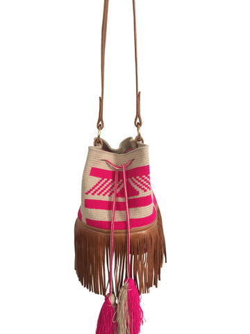 Image of Wayuu bucket bag purse with brown leather strap and fringe; bag is tan with pink design