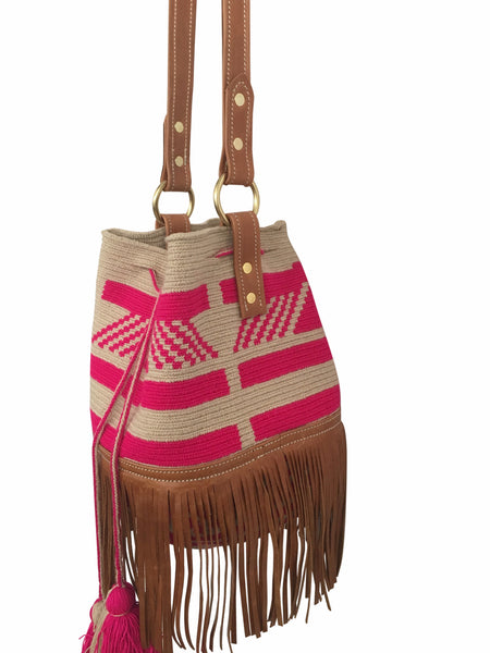 Side angle image of Wayuu bucket bag purse with brown leather strap and fringe; bag is tan with pink design