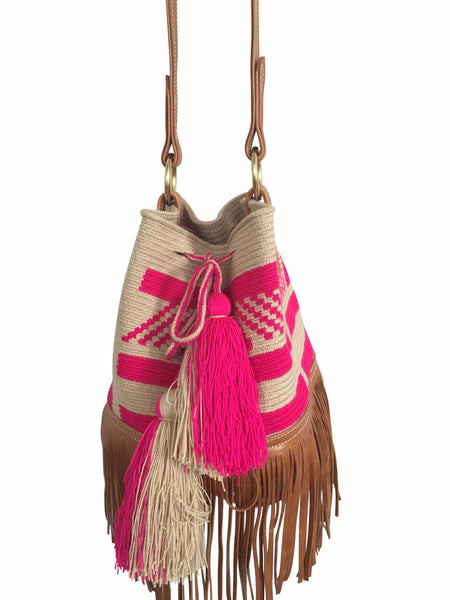 Close up image of Wayuu bucket bag purse with brown leather strap and fringe; bag is tan with pink design