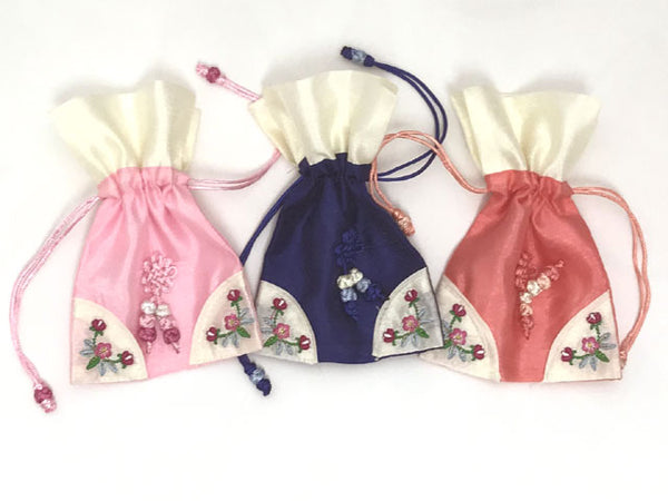 Three pretty drawstring pouches in pink, royal blue, and coral
