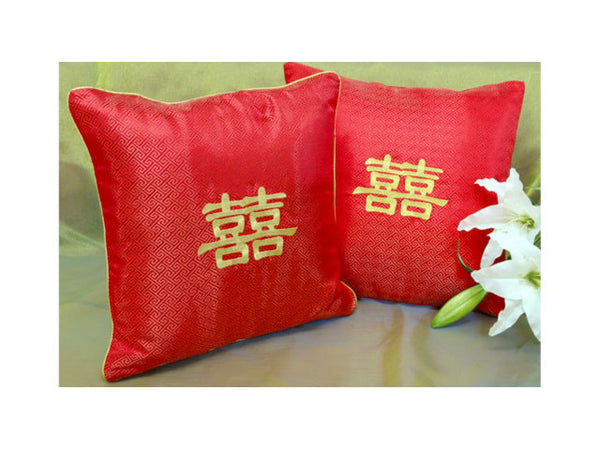 Two red silk pillows with an embroidered Chinese double happiness character