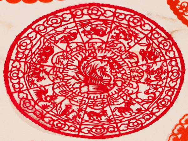 Intricate red paper cut decoration featuring the animals of the Chinese zodiac and a phoenix at the center