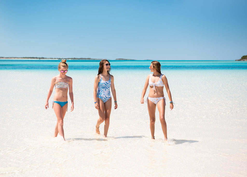 Girls walking in the Bahamas on White Sand and through Crystal Clear Waters wearing Chance Loves Swimwear