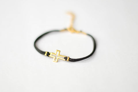 Women's bracelet with gold tone outline cross charm, black cord