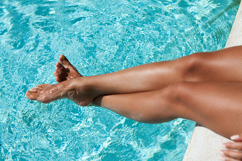 woman dipping tan legs in pool
