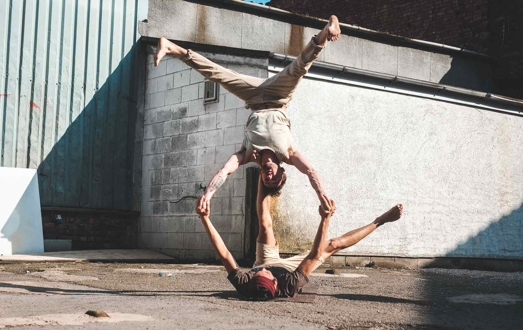 Two men doing acro yoga poses wearing so we flow...