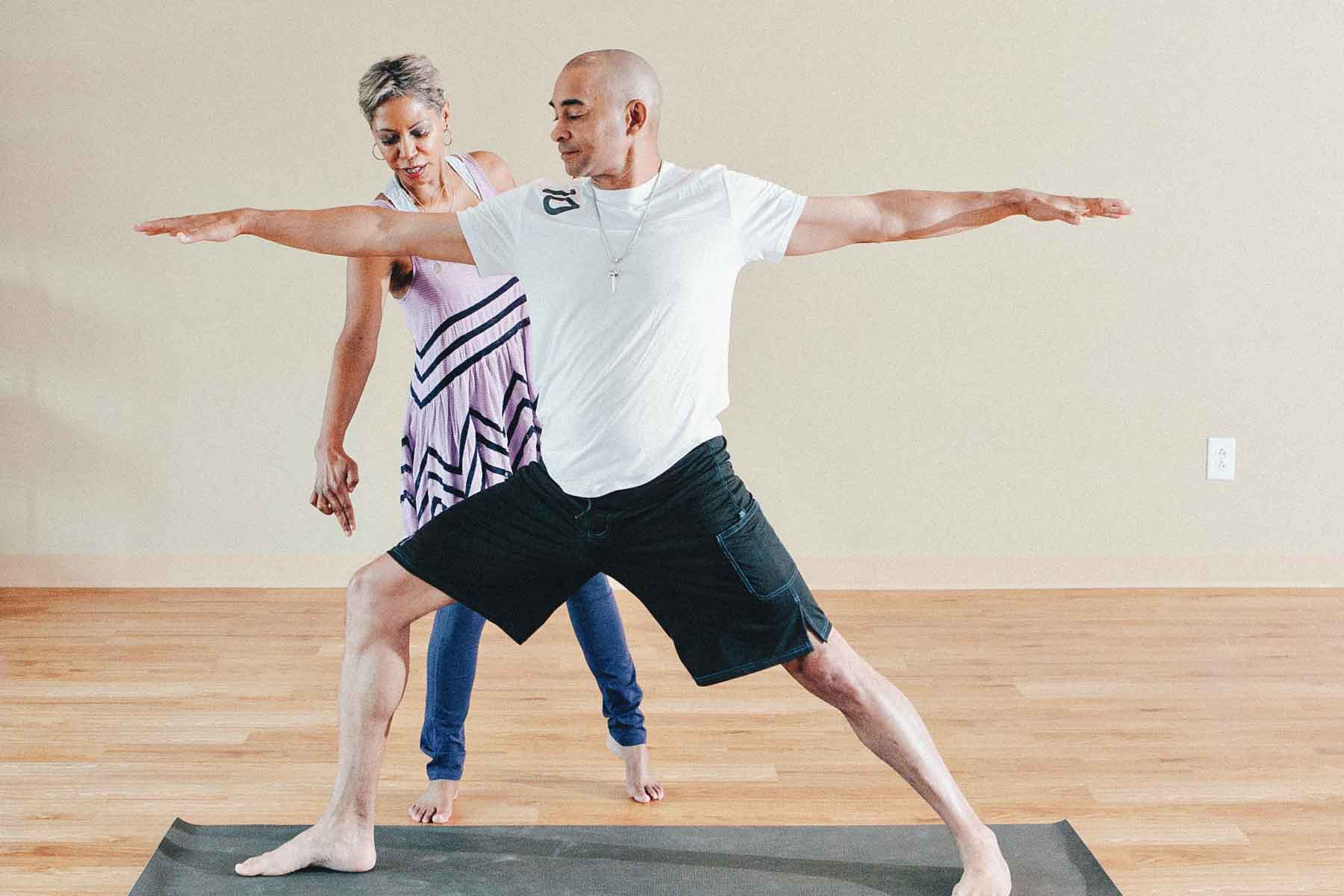 Female yoga teacher assisting male yoga student in warrior two pose