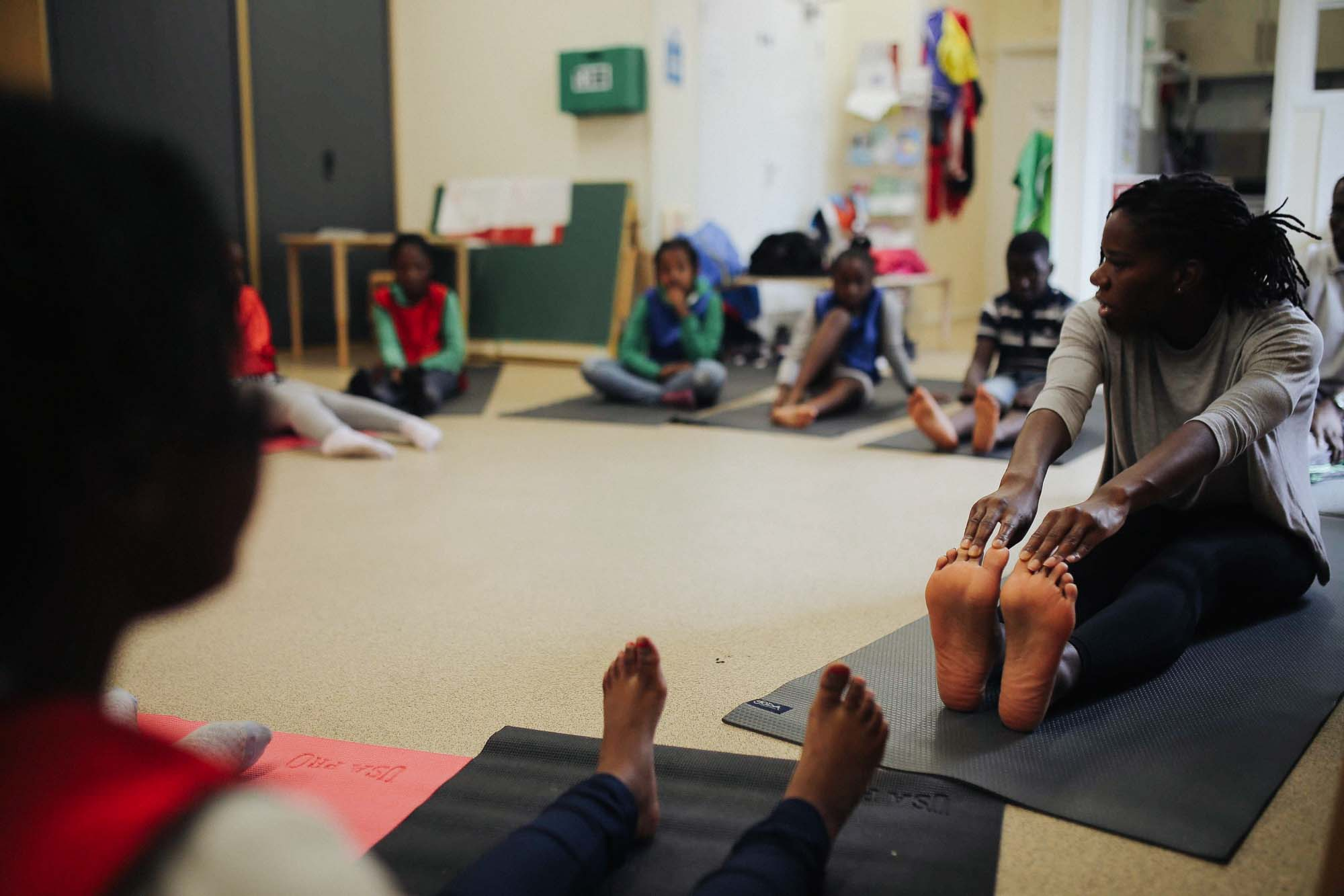 Amani Eke from Project Yogi teaching yoga to school children in a classroom