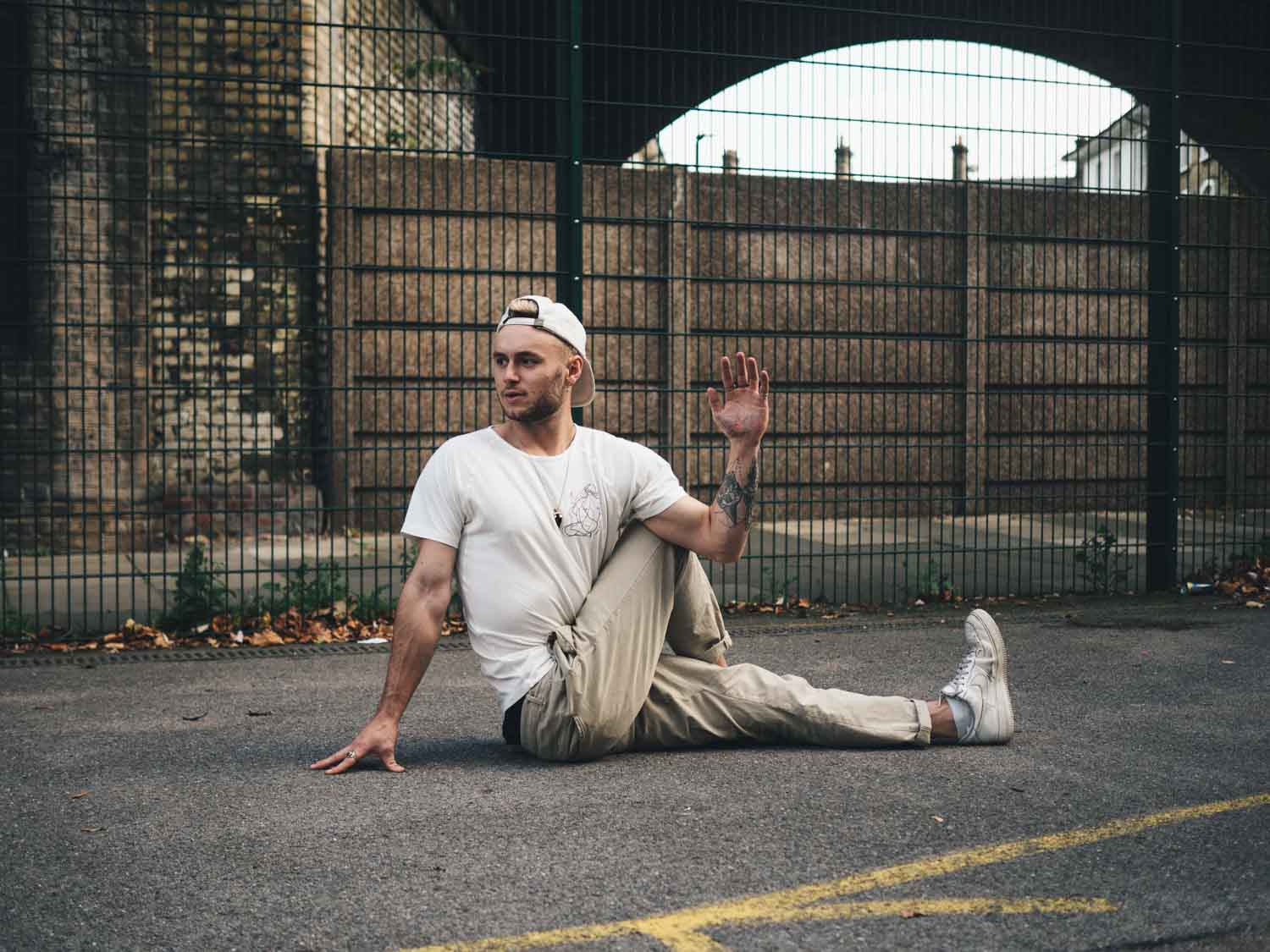 Max Munro wearing so we flow... Mysore Room 1 T-shirt in a seated twist pose