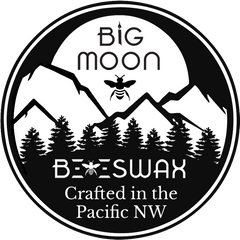 big moon beeswax logo with large moon over mountains and a bee in front of the moon