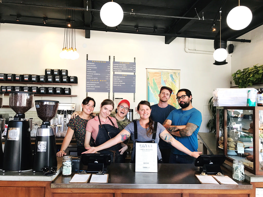 6 young members of the Dune team stand behind the counter with smiles at our Anacapa location.