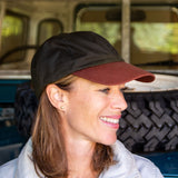 olive green wax sports cap with brown peak on woman