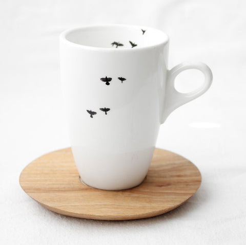 White coffee mug with bird print and wooden Saucer