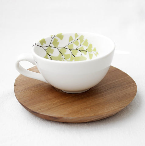 White espresso cup with fern design and wooden saucer