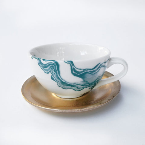 White espresso cup with teal mineral print and brass saucer