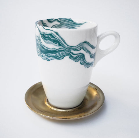 White coffee mug with teal mineral print and brass metal saucer