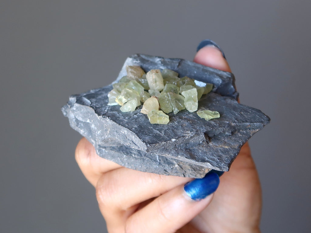 hand holding green apatite gemstones on gray fossil rock at satin crystals