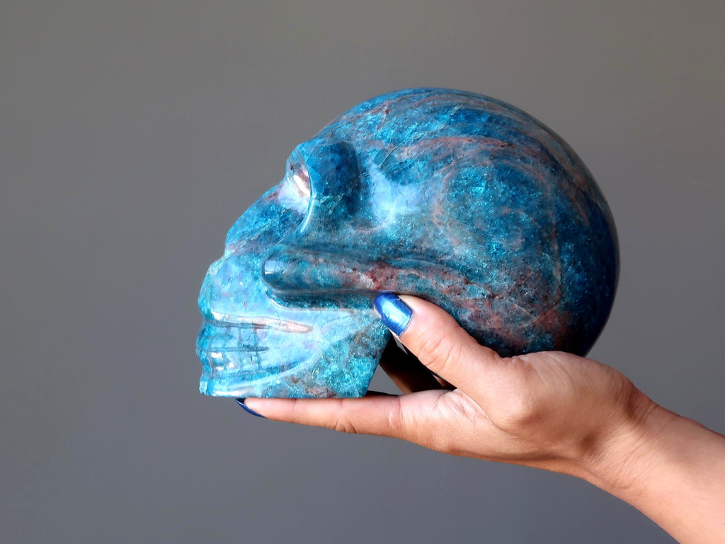 hand holding a big blue apatite gemstone skull carving at satin crystals