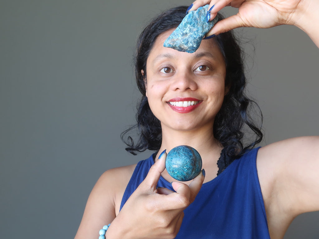 sheila of satin crystals holding a raw blue apatite rock and polished sphere over her chakras for healing