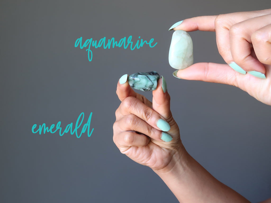 hands holding aquamarine and emerald tumbled stones