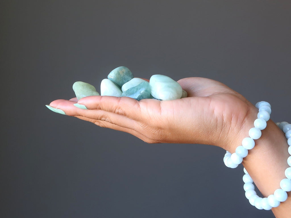 hand wearing aquamarine stretch bracelets holding a pile of aquamarine tumbled stones