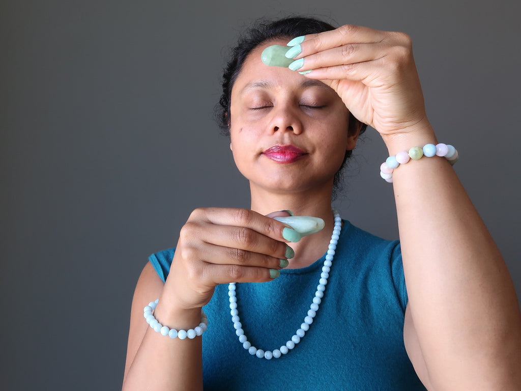 sheila of satin crystals holding up aquamarine tumbled stones over her third eye and throat chakras