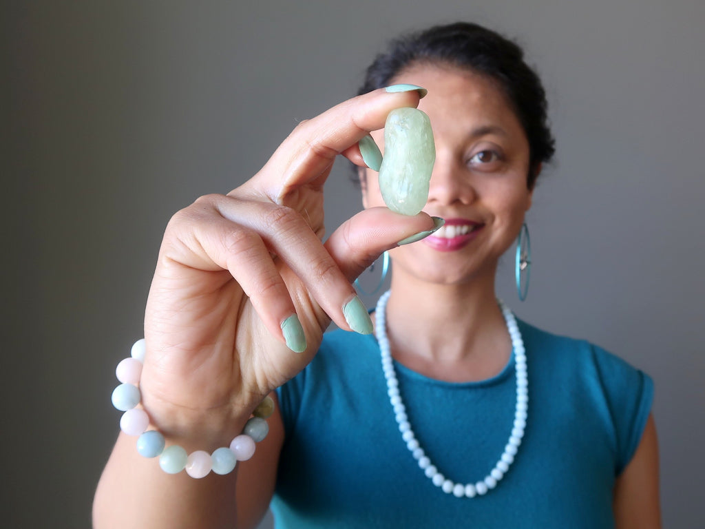 sheila of satin crystals holding up an aquamarine tumbled stone