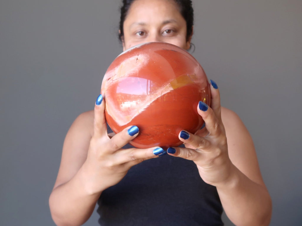 sheila of satin crystals gazing into a big red jasper sphere