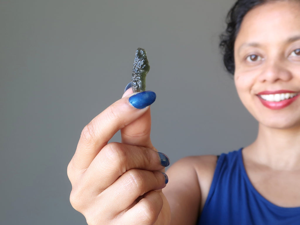 sheila of satin crystals holding up a gemmy green moldavite meteorite