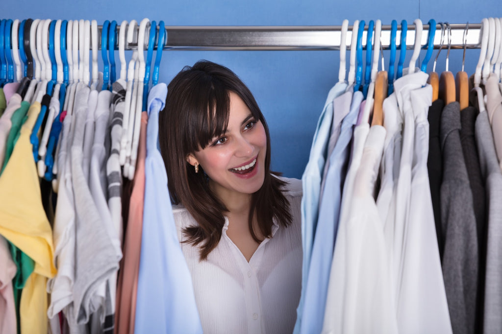 happy lady with tops, shirts and tshirts in wardrobe