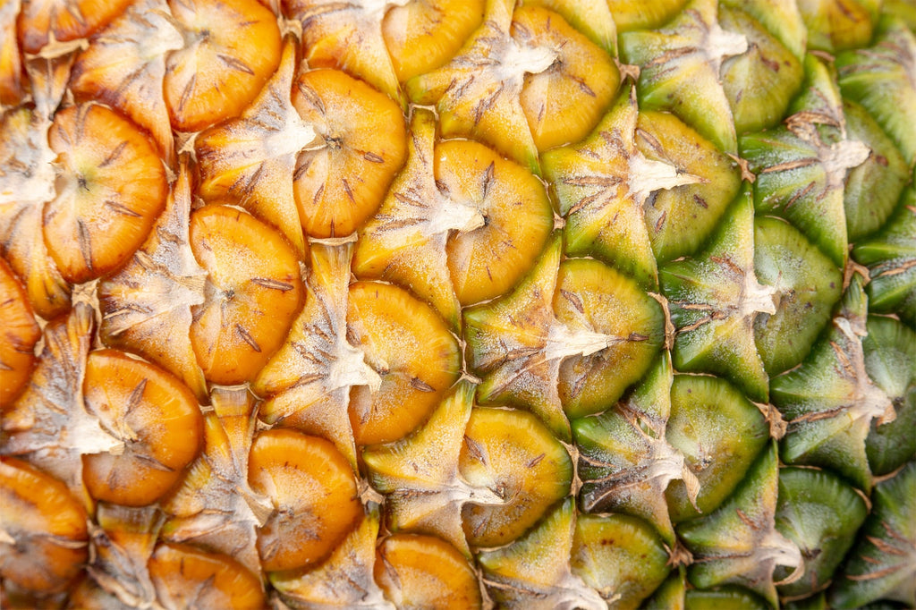 close up of yellow and green pineapple skin