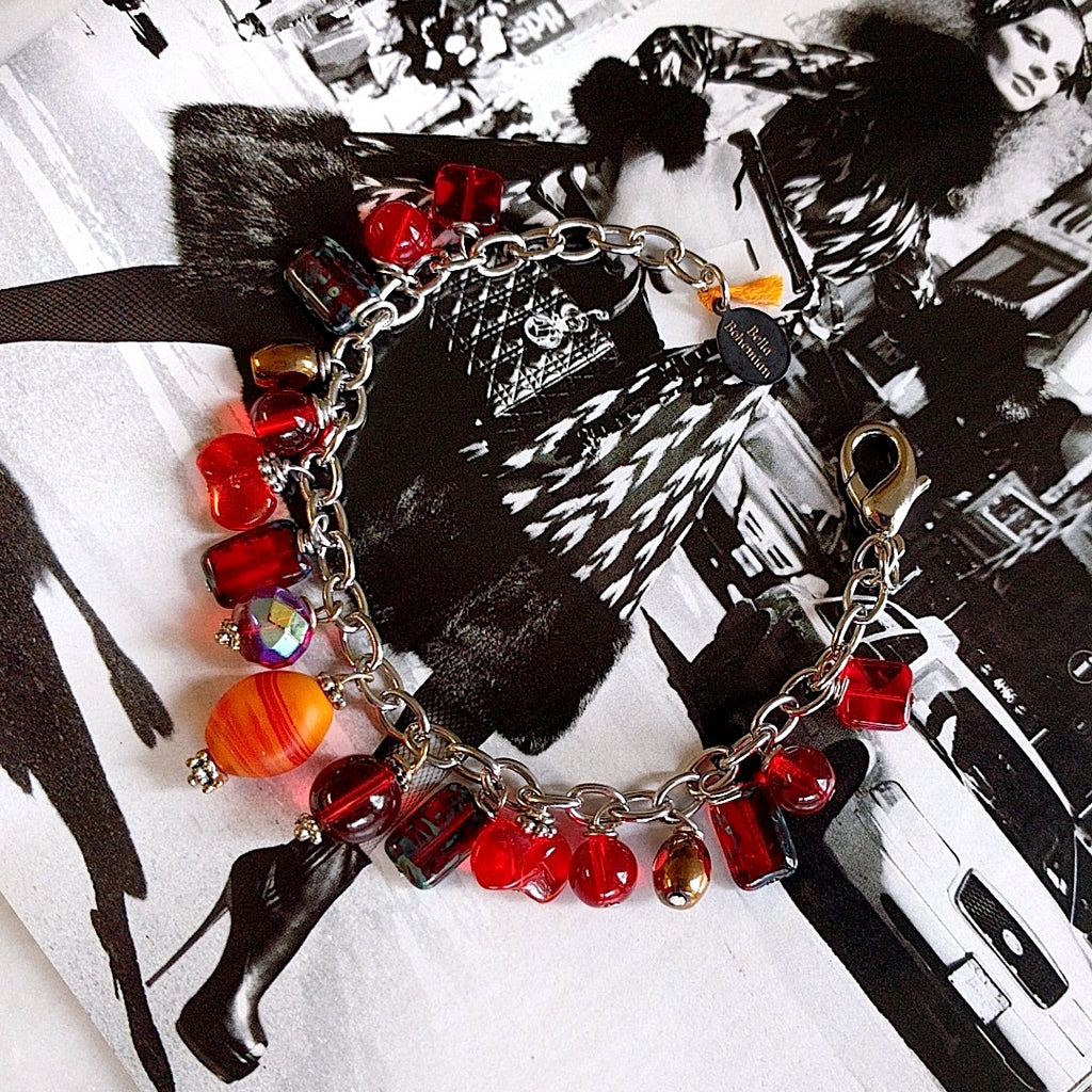 handmade silver-plated charmed bracelet with fire red polished Czech glass beads on alternate background