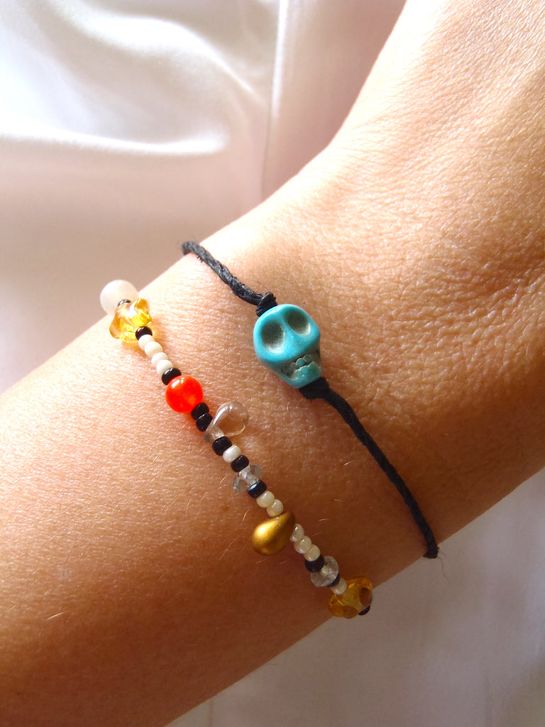 set of bracelets, one with black cotton thread, the other with multicolored seed and glass beads shown on a lady's wrist