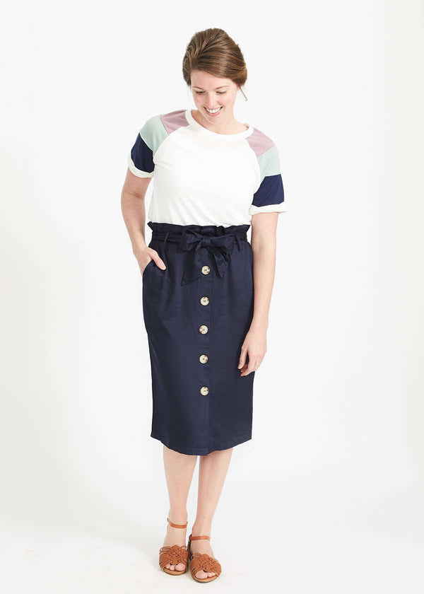 Woman wearing a navy button front paper bag style midi skirt.